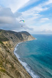 Flying tandem paragliders over the sea close to mountains, vertical view of the landscape Royalty Free Stock Photo