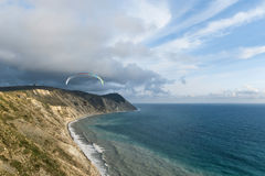 Flying tandem paragliders over the sea and near the mountains, beautiful landscape view Stock Photos