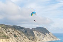Flying tandem paragliders over the sea and near the mountains, beautiful landscape view stock photo