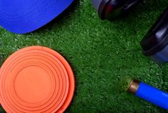 Flying target plate, cap, noise suppression headphones and a patron. On artificial grass royalty free stock photo
