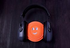 Flying target plate with cute face in noise suppression headphones. Against the dark background stock images