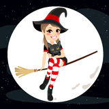 Flying Teenager Witch Cat. Cute teenager witch holding pet cat flying with broom on full moon Halloween dark night Stock Images