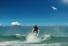 Flying to sun. Jet ski & bird. Jet-ski is racing and jumped up (free ride) above the beautiful waves and foam. The white bird if flying in the blue sky Stock Photos
