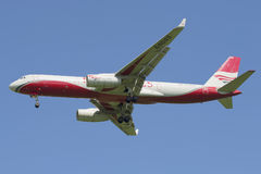 Flying the TU-204-100B (RA-64043) airline Red Wings against the blue sky Stock Photos