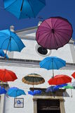 Flying umbrellas. I took this picture in Evora, Portugal. It was a sunny day, but several colored umbrellas were in front of this little white church Royalty Free Stock Photography