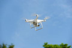 Flying unmanned quadcopter with video camera.  Stock Photos