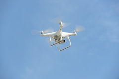 Flying unmanned quadcopter with video camera.  Royalty Free Stock Photography