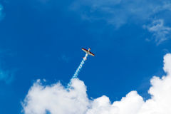 Flying up plane. Red and white sport plane flies up releasing a stream of smoke into the blue sky with clouds royalty free stock images