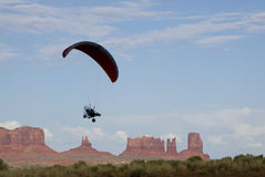 Flying in the Valley. A powered paraglider pilot in flight over Monument Valley Stock Photography