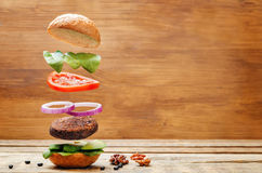 Free Flying Vegan Black Bean Mushrooms Burger Royalty Free Stock Photography - 84242837