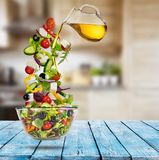 Flying vegetable greek salad with pouring olive oil from saucer. Blur kitchen on background. Healthy eating and lifestyle. Very high resolution image Royalty Free Stock Image