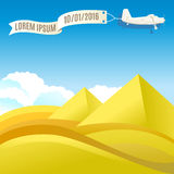 Flying vintage plane with banner and pyramids, desert landscape. Royalty Free Stock Photo