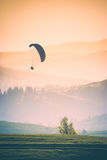Flying in a warm light. Instagram stylisation. Paraglide silhouette flying over misty mountain valley in a warm light of sunrise. Instagram stylisation Royalty Free Stock Photography