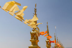Flying and waving yellow and orange buddhist flags in thai temple with sky background Royalty Free Stock Images