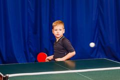 Flying white ball in table tennis. A child plays table tennis royalty free stock photo