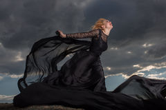 Flying in the wind. Blond in a long black dress stand against the background of gray clouds Royalty Free Stock Photography