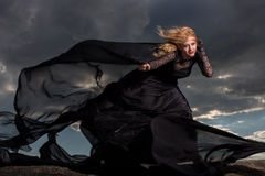 Flying in the wind. Blond in a long black dress stand against the background of gray clouds Stock Photo