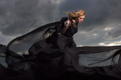 Flying in the wind. Blond in a long black dress stand against the background of gray clouds Stock Photography