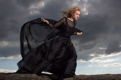Flying in the wind. Blond in a long black dress stand against the background of gray clouds Royalty Free Stock Photo