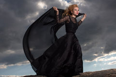 Flying in the wind. Blond in a long black dress stand against the background of gray clouds Royalty Free Stock Images