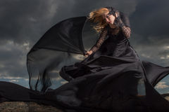 Flying in the wind. Wind blowing blond hair and long black dress of the young girl standing on the mount Royalty Free Stock Photos