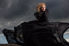 Flying in the wind. Wind blowing blond hair and long black dress of the young girl standing on the mount Stock Photos