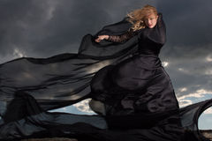 Flying in the wind. Wind blowing blond hair and long black dress of the young girl standing on the mount Stock Images