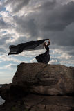 Flying in the wind. The girl in her black dress standing on the mount against the background of gray clouds Stock Photos