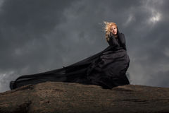 Flying in the wind. The girl in her black dress standing on the mount against the background of gray clouds Royalty Free Stock Photo
