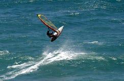 Flying Windsurfer Windsurfing in Hawaii. A windsurfer jumping a wave while sailboarding in Honolulu, Hawaii Stock Photography