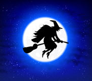 Flying witch on a broomstick on the background of the full moon Royalty Free Stock Photo