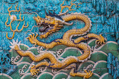 Flying yellow imperial dragon on the wall. Flying yellow imperial dragon with waves, clouds and silhouettes of mountain on the famous nine dragon wall in the Stock Photo