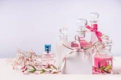 Flyktiga dofter för doft och för skönhetsmedel Sammansättning av flaskor med blommor och det tomma hälsningkortet med bandet, frä Royaltyfri Foto