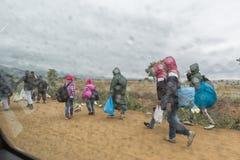 Flyktingar och migranter som går den dammiga vägen i regnet till Royaltyfria Foton