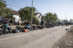 Flyktingar som bildar en väntande linje i Tovarnik Arkivbild
