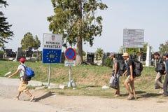 Flyktingar som framme passerar av EU-ingångstecknet framme av denKroatien gränsövergången av Sid Tovarnik på den Balkans rutten arkivfoto