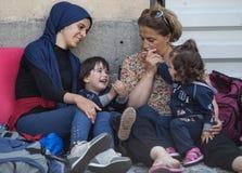 Flyktingar som tröstar deras barn på den Keleti drevstationen i Budapest Arkivfoton