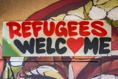 Flyktingar välkomnar grafittitecknet royaltyfria bilder