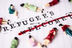 Flyktingar välkomnar strikethroughtext på papper royaltyfri fotografi