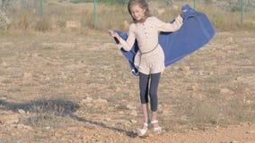 Flyktingflickan spelar på förlorad jordning i flyktinglägret flickadans med en filt i hennes händer begreppsarmod och lycka arkivfilmer