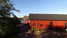 Flyover των ironoxide-χρωματισμένων ξύλινων κτηρίων και του άσπρου φάρου, βίντεο κηφήνων απόθεμα βίντεο