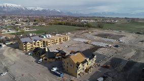 Flyover of Construction Site of Planned Community Near Farmland in Utah. Aerial footage of apartments under construction in American Fork, UT, near public stock video footage