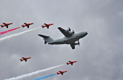 Flypast of RAF Red Arrows escorting an Airbus A400M Royalty Free Stock Photography