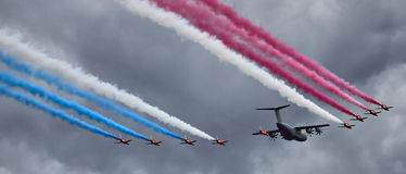 Flypast of RAF Red Arrows escorting an Airbus A400M. Red Arrows and Airbus A400M transport at a UK airshow Royalty Free Stock Images