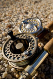 Flyrods Closeup. Closeup of two fly rods and reels sitting on small pebbles Royalty Free Stock Photo