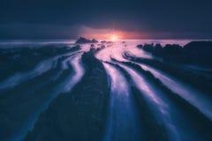 Flysch vaggar i den barrika stranden på solnedgången royaltyfria foton