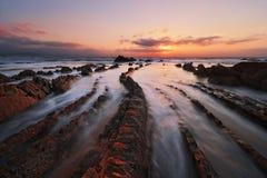 Flysch vaggar i den barrika stranden på solnedgången Fotografering för Bildbyråer