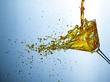 Flytandefotografi Alldeles av små små droppar för alkoholdrink som hälls ut ur det klara vinexponeringsglaset royaltyfri bild