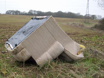 Flytipped armchair. Upside down on the edge of a field with a background of arable fields, pylons and trees Stock Photos