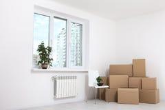 Flytta sig in i en ny lägenhet Flytta massor av kartonger i en tom ny lägenhet Arkivfoto